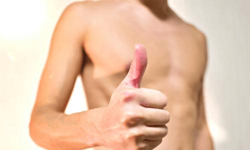 親指を立てる裸の男性の写真