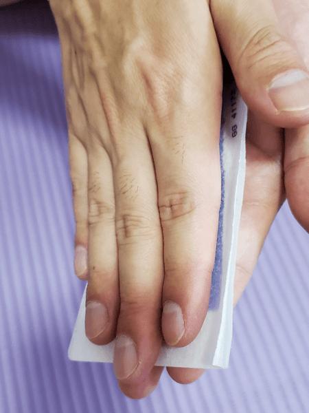 ボディヘアリムーバルワックスストリップスを両手で挟んで温めている写真